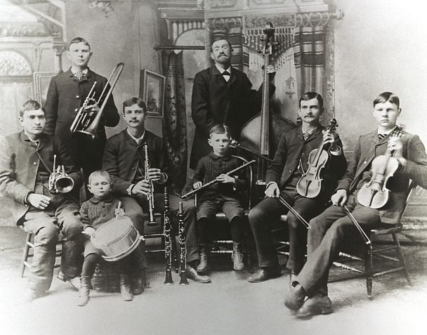 It's a historic picture of one grownup and 7 children, which all have instruments. It's the pic of a music band. 6 children are sitting, one boy is standing behind them and next is the grownup. It's the Bach band from Rochester, N.Y.